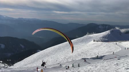 coldness : paraglider flying among snowy peaks in a ski resort in the Caucasus mountains Stock Footage