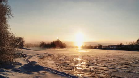 snowy background : winter frosty sunset over the frozen snow-covered river