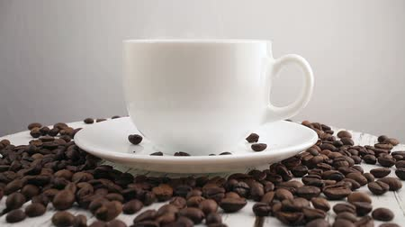vaření v páře : White cup with black, hot coffee standing on brown, roasted beans on sacking