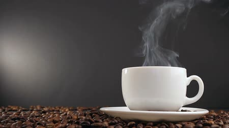 hot beverage : cup with hot drink on roasted coffee beans. dolly shot