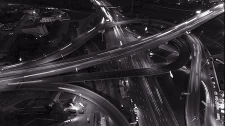 capacidade : Overhead flyover the complex road junction highway. Night Light, sunset. High altitude drone flight.