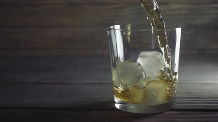 бурбон : Whisky is poured into glass in slow motion