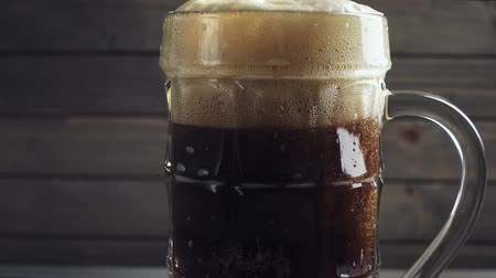 fabricado cerveja : Pouring Cold Dark Beer into beer mug. Over dark wooden background. Slow motion