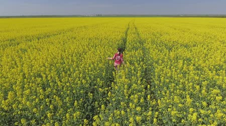 canola : Pretty young girl walks and turns around in the rape field