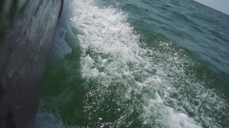 водный путь : Powerful waves pulled out from fast moving boat, a huge stream of deep blue water with white foam rising up