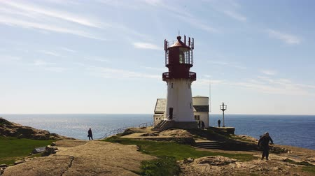 farol : Video of Lindesnes beacon in summer, South Norway. Aerial shot. Rocky sea coast and blue sky. Stock Footage