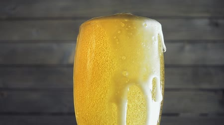 официант : Beer poured in glass on wood background. Slow motion Стоковые видеозаписи
