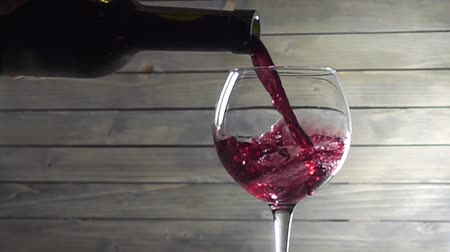 winnica : Pouring red wine into the glass against wooden background. Slow motion