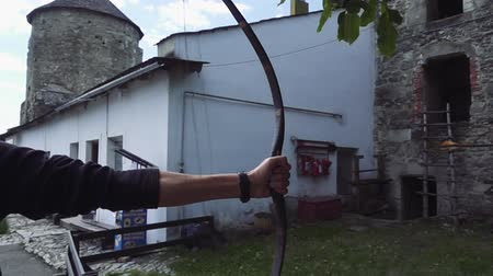 tiro com arco : Close up shot of archer with strong hands bending mechanic bow arrow concentrating on target Stock Footage