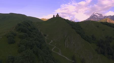 ortodoxia : Aerial view. The Gergeti Church on background of Kazbek Stock Footage