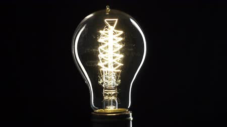 meggyullad : Edisons light bulb illuminates slowly from electric current Stock mozgókép