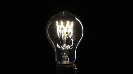 изобретение : Edisons light bulb on black background Стоковые видеозаписи