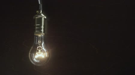 The light bulb slowly lights up, quickly flickers on a background from a wood