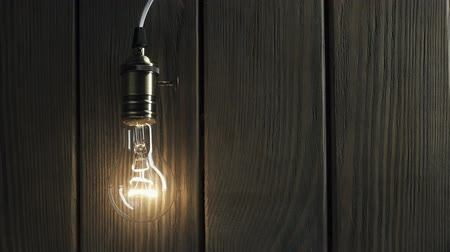 light bulb illuminates on wooden background Filmati Stock
