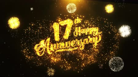 jubileu : 17th Happy Anniversary Text Greeting and Wishes card Made from Glitter Particles From Golden Firework display on Black Night Motion Background. for celebration, party, greeting card, invitation card.