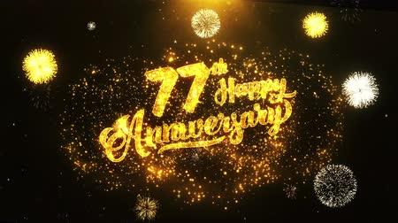 jubileu : 77th Happy Anniversary Text Greeting and Wishes card Made from Glitter Particles From Golden Firework display on Black Night Motion Background. for celebration, party, greeting card, invitation card.