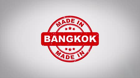 papírnictví : Made In BANGKOK Signed Stamping Text Wooden Stamp Animation. Red Ink on Clean White Paper Surface Background with Green matte Background Included.
