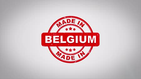 papírnictví : Made In BELGIUM Signed Stamping Text Wooden Stamp Animation. Red Ink on Clean White Paper Surface Background with Green matte Background Included.