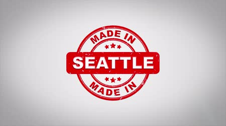 papírnictví : Made In SEATTLE Signed Stamping Text Wooden Stamp Animation. Red Ink on Clean White Paper Surface Background with Green matte Background Included.