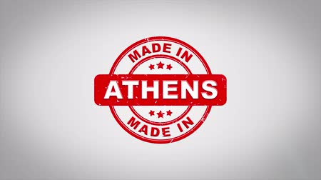 papírnictví : Made In ATHENS Signed Stamping Text Wooden Stamp Animation. Red Ink on Clean White Paper Surface Background with Green matte Background Included.