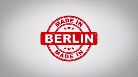 сделанный : Made In BERLIN Signed Stamping Text Wooden Stamp Animation. Red Ink on Clean White Paper Surface Background with Green matte Background Included.