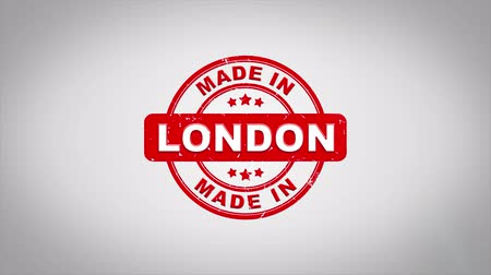 papírnictví : Made In LONDON Signed Stamping Text Wooden Stamp Animation. Red Ink on Clean White Paper Surface Background with Green matte Background Included.