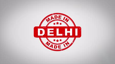 rubberstempel : Made In DELHI Ondertekend Stamping Text Wooden Stamp Animation. Rode inkt op schone achtergrond van wit papier met groene achtergrond in achtergrond.