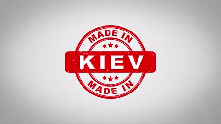 papírnictví : Made In KIEV Signed Stamping Text Wooden Stamp Animation. Red Ink on Clean White Paper Surface Background with Green matte Background Included.