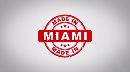 applying : Made In MIAMI Signed Stamping Text Wooden Stamp Animation. Red Ink on Clean White Paper Surface Background with Green matte Background Included.