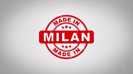 papírnictví : Made In MILAN Signed Stamping Text Wooden Stamp Animation. Red Ink on Clean White Paper Surface Background with Green matte Background Included.