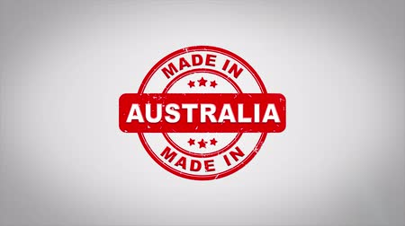 applying : Made In AUSTRALIA Signed Stamping Text Wooden Stamp Animation. Red Ink on Clean White Paper Surface Background with Green matte Background Included. Stock Footage