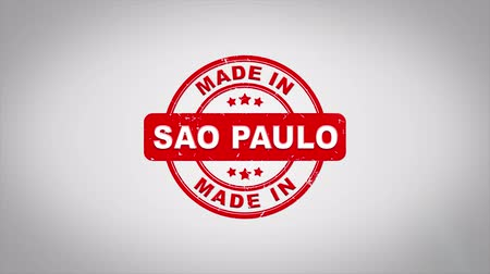 бразильский : Made In SAO PAULO Signed Stamping Text Wooden Stamp Animation. Red Ink on Clean White Paper Surface Background with Green matte Background Included.