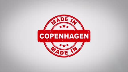 danimarka : Made In COPENHAGEN Signed Stamping Text Wooden Stamp Animation. Red Ink on Clean White Paper Surface Background with Green matte Background Included.