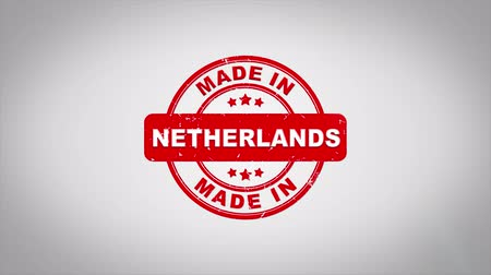 papírnictví : Made In NETHERLANDS Signed Stamping Text Wooden Stamp Animation. Red Ink on Clean White Paper Surface Background with Green matte Background Included.
