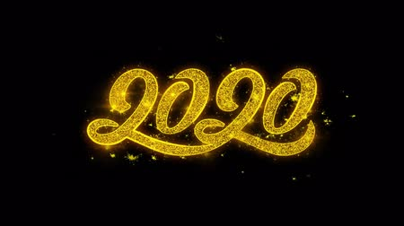 escrito : 2020 New Year Typography Written with Golden Particles Sparks Fireworks Display 4K. Greeting card, Celebration, Party Invitation, calendar, Gift, Events, Message, Holiday, Wishes Festival