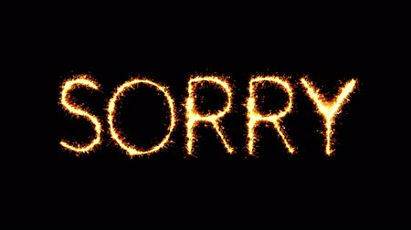 apologize : I Am Sorry Text Sparkler Writing With Glitter Sparks Particles Firework on Black 4K Loop Background. Greeting card, Invitation, Celebration, Party, Gift, Message, Wishes, Festival. Stock Footage