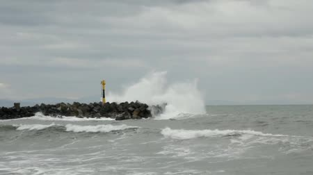 világítótorony : Waves on a concrete jetty with a little lighthouse