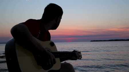 serenade : boy plays on guitar at sunset