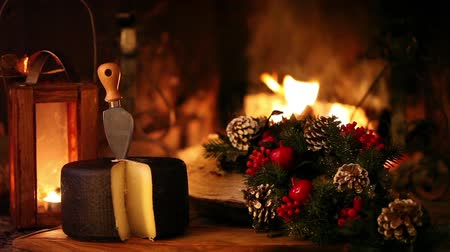 şömine : Video clip of nice Christmas scene in front of the fireplace, showing typical Italian seasoned cheese and Christmas decorations.