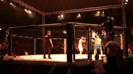 lutador : ROME, ITALY - JUNE 13, 2014: Third edition of Impera FC MMA Championship in Italy at the Palace of Sports in Viale Tiziano. Video of Giuliano Pennese fighting in the cage against Elia Madau .