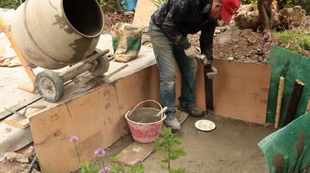 müteahhit : Artificial pond construction - mason sticking wood slat inside fresh cement in order to reinforce the wall of the basin. Stok Video