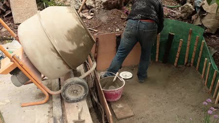vivarium : Video clip of mason reinforcing the fresh cement during the construction of artificial pond in the garden.