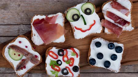 crostini : Video clip of various appetizers canape style on toasted bread with cheese, cucumbers, olives, red peppers and ham.