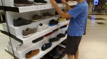 buty sportowe : FIUMICINO, ITALY - SEPTEMBER 2, 2016: Man shopping shoes at Geox inside Parco Leonardo Shopping Center. Geox is an Italian brand of shoe and clothing manufactured with waterproofbreathable fabrics.