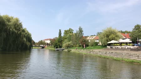 лодки : LJUBLJANA, SLOVENIA - AUGUST 29, 2018: Fresco cafes and restaurants on the banks of Ljubljanica river. Стоковые видеозаписи