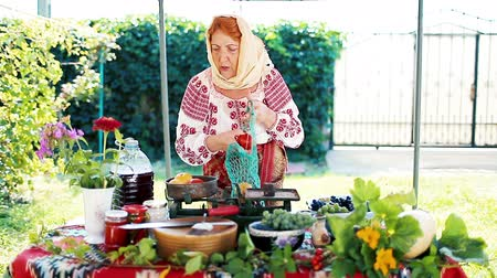 hímzés : Romanian peasant selling local products from her garden.