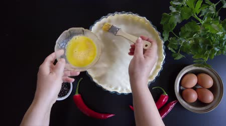 baking dishes : Woman hands press the edges of a savory pie with their fingers to close them, then brush the surface with egg yolk.