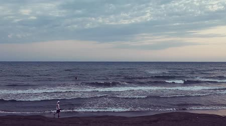 A Mediterranean beach in the evening with a man doing  surf in the water and a boy walking along the shore.