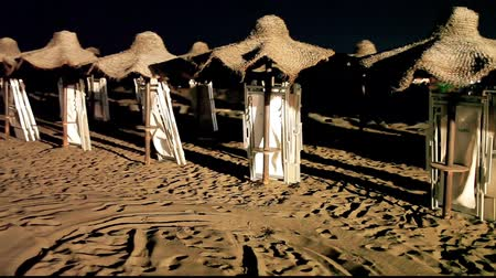 Straw umbrellas arranged in a row, on a beach in the summer, by night.