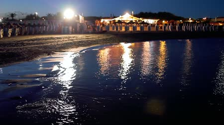 Small beach at night, with lights reflected in the calm water.